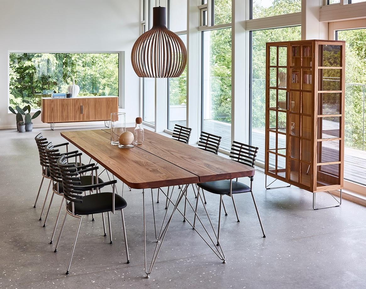 Moderne spisestue med langt spisebord med treplate og tynne alumiumsben. 6 moderne svarte stoler inntil bordet og ei stor lampe henger over.